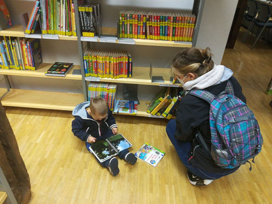 Kind mit Mutter in der Bibliothek